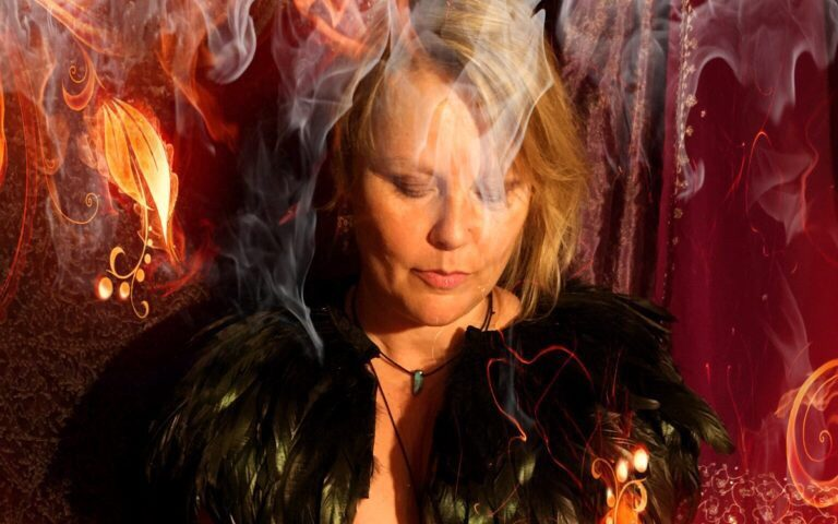 a photo about me with flames and smoke and feathers draped over my shoulders